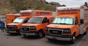 Mold Damage Restoration Vans And Trucks At Job Site