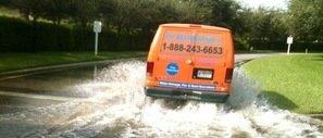 Water Damage East Garden City Restoration Van Driving Down Flooded Street